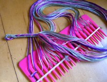 in-progress fingerloop braid 'resting' on a wide-tooth comb holder