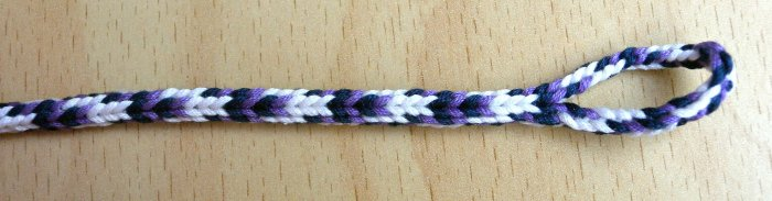 7-loop round 'spanish' -type fingerloop braid, made by Ingrid Crickmore. Braid invented/ discovered - and 'Spiaggian Eagle' color-pattern designed by Douglas Grant.