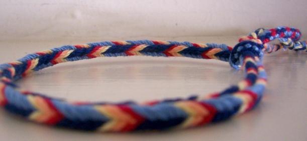 Caroline Spinali, bracelet, 7-loop square braid (4 loops bicolor blue/light blue, 1 yellow, 1 orange, 1 red)