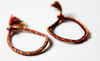 "Faustine Ferhmin, bracelets. Loop braided square braids. Left braid has ""Chevrons over Bicolor stripes"" pattern, right has an ""Edge"" pattern variation with a contrasting gold shank to one loop (see bicolor loop tutorial)."