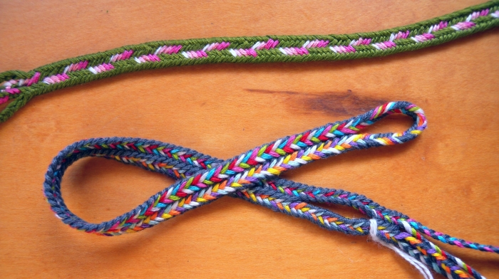 two 9-loop flat fingerloop braids having color patterns that require linking. Loop manipulation/ loop braiding
