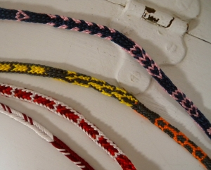 Fingerloop braids of various types with pickup patterns, made by Ingrid Crickmore.