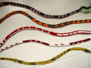 various fingerloop braided braids with pickup-type patterning, made by Ingrid Crickmore