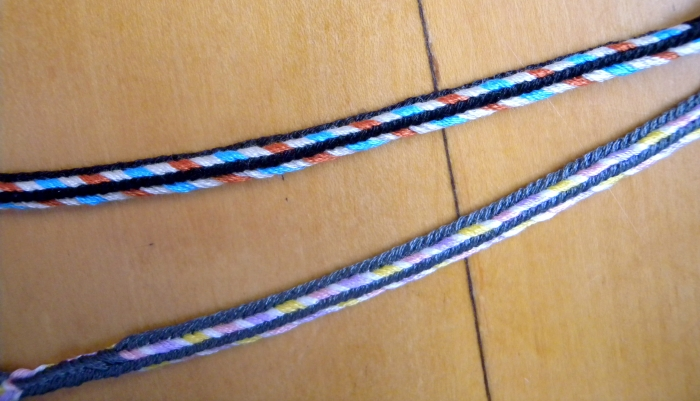 """2 Triangle braids with variations of the """"Edge"""" color-pattern, fingerloop braiding, Ingrid Crickmore"""