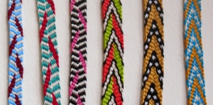Fingerloop braided plain weave (plain oblique interlaced) repp braids of 12-16 loops, fingerloop braiding, cotton embroidery floss, by Ingrid Crickmore / loopbraider.com